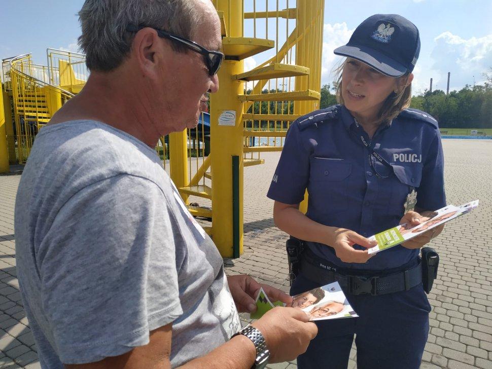 Zdjęcie kolorowe: policjantka katowickiej komendy podczas rozmowy ze starszą osoba o bezpieczeństwie i zasadach postępowania z oszustami