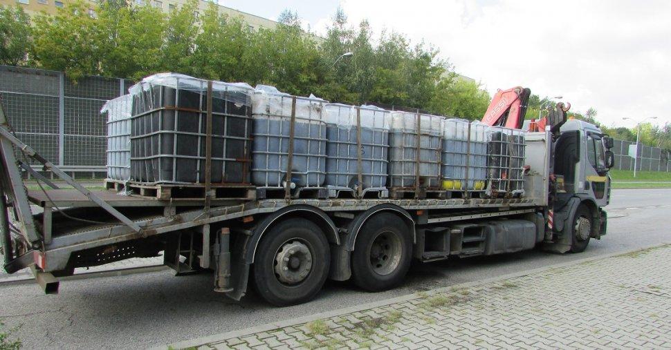 Zdjęcie kolorowe: samochód ciężarowy marki Renault Premium przystosowany do świadczenia usług w zakresie pomocy drogowej, który przewoził 12 pojemników typu mauser z nielegalnymi odpadami