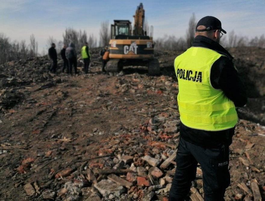 zdjęcie kolorowe: policjant na miejsu ujanwionego nielegalnego składowisk odpadów