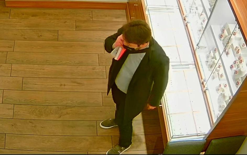 zdjęcie kolorowe: screen z monitoringu sklepowego przedstawiający mężczyznę ubranego w ciemne spodnie, ciemny płaszcz, szary sweter z założona czarna maseczka ochronna na twarzy i rozmawiający przez telefon komórkowy, lewy profil