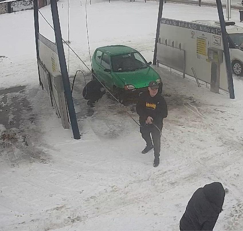 zdjęcie kolorowe: teren myjni samochodowej, zaparkowany zielony samochód osobowy i trzech mężczyzn podejrzewanych o jej zniszczenie