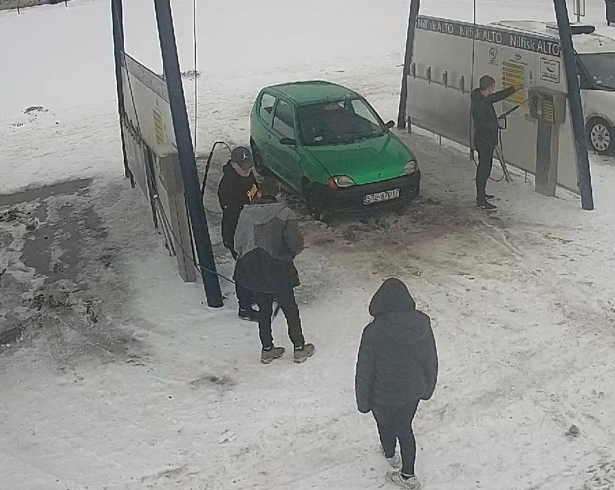 zdjęcie kolorowe: teren myjni samochodowej, zaparkowany zielony samochód osobowy i trzech mężczyzn podejrzewanych o jej zniszczenie  oraz świadek
